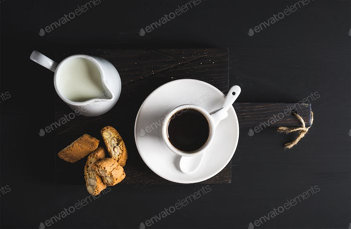 Cup of hot espresso, creamer with milk and cookies on dark rustic wooden board over black background