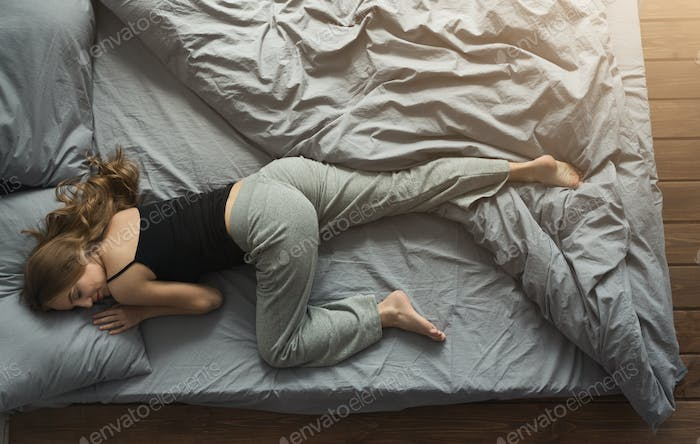 Peaceful woman sleeping in bed at home