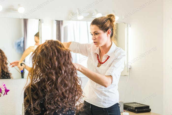 Hairdresser doing haircut for women in hairdressing salon