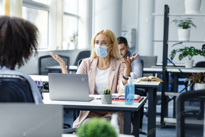 Conflict at work and problems with project. Angry woman in protective mask at workplace with laptop
