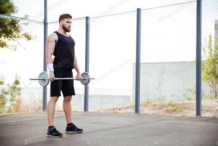 Muscular fitness man doing heavy exercise using barbell