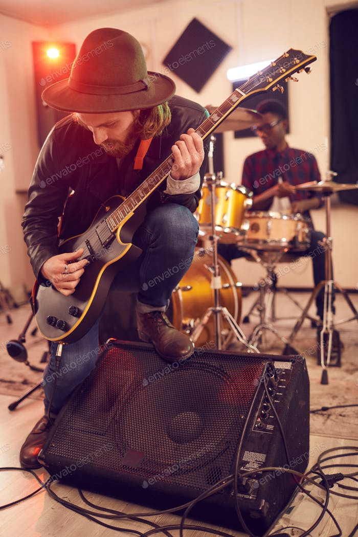 Young Man Playing Guitar at Rehearsal