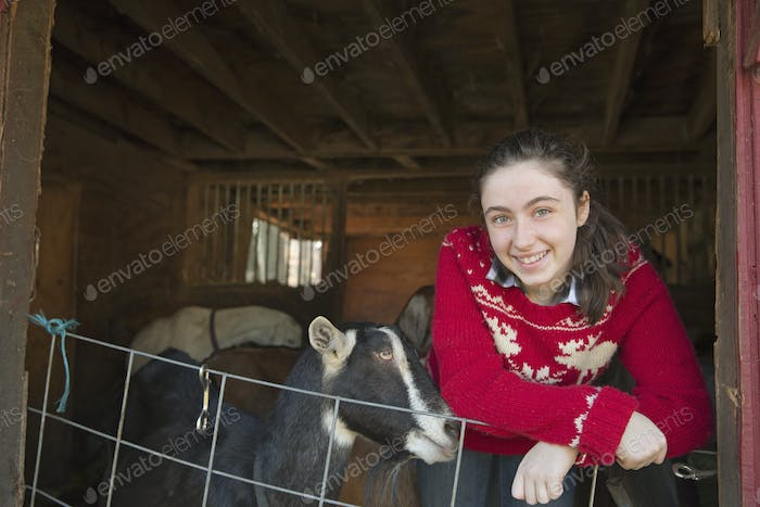 A goat farm. A young girl leaning on the barrier of the goat shed, with a group of goats behind her.