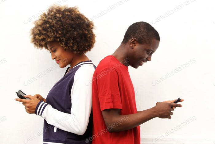 african couple standing back to back holding mobile phones