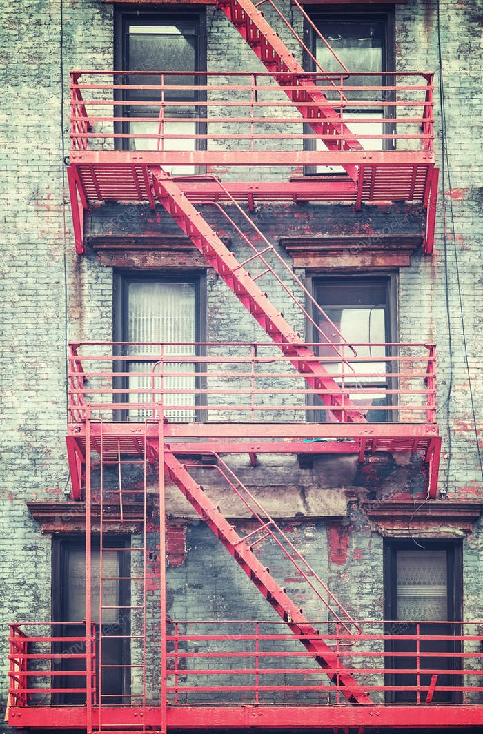 Retro stylized photo of red fire escape in Manhattan.