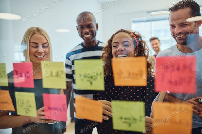 Laughing group of designers brainstorming together in an office