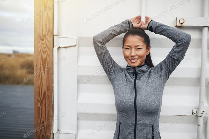 Young Asian woman in exercise gear standing outside before jogging