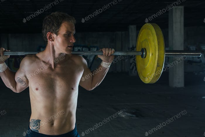 Man lifting barbell in abandoned building