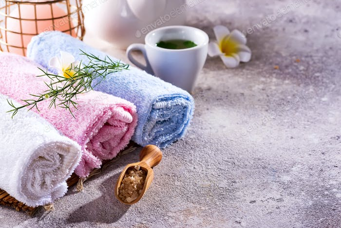 Wellness setting. Sea salt , towel, tea and flowers on stone background. Space for copy