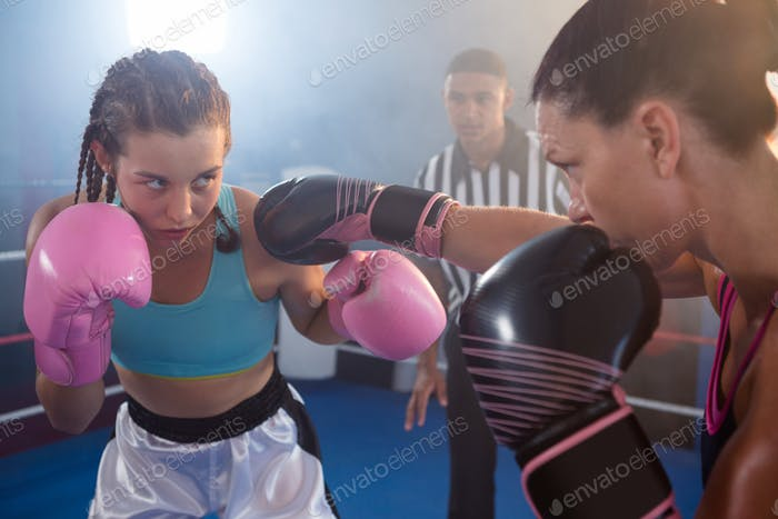 Female boxers fighting in ring