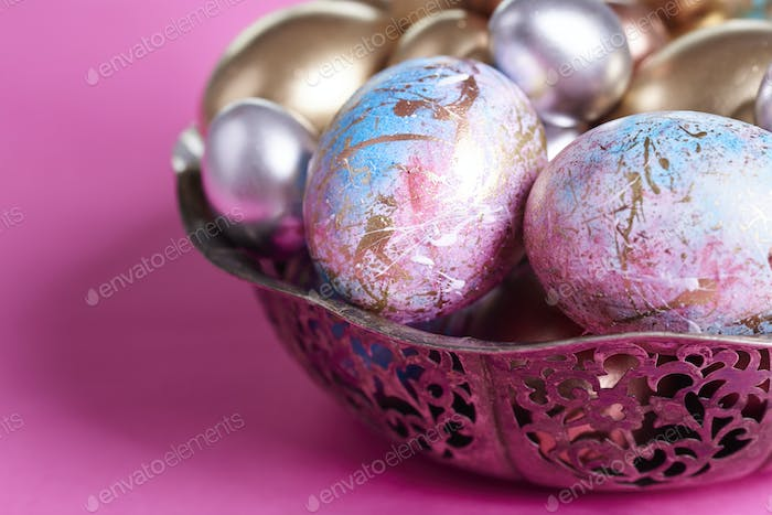 Ornate eggs in wire basket on purple background