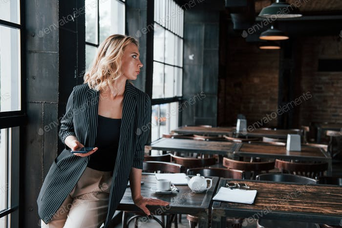 Wireless technologies. Businesswoman with curly blonde hair indoors in cafe at daytime