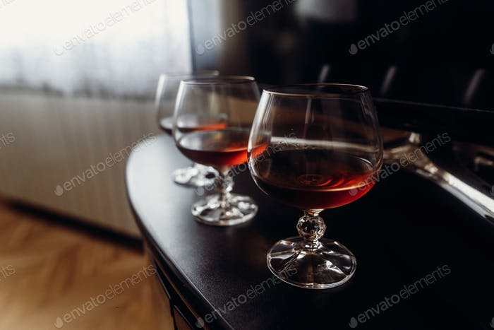 Expensive glasses with whiskey on dark wooden table closeup