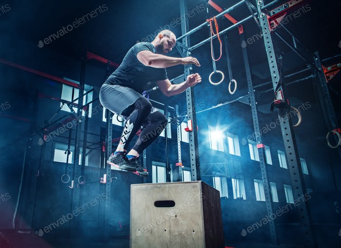 Man jumping during exercises in the fitness gym. CrossFit.