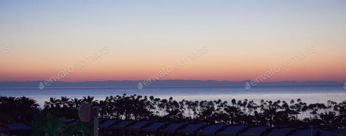 Beautiful colorful sunset over the sea and the sun shines. Orange sky
