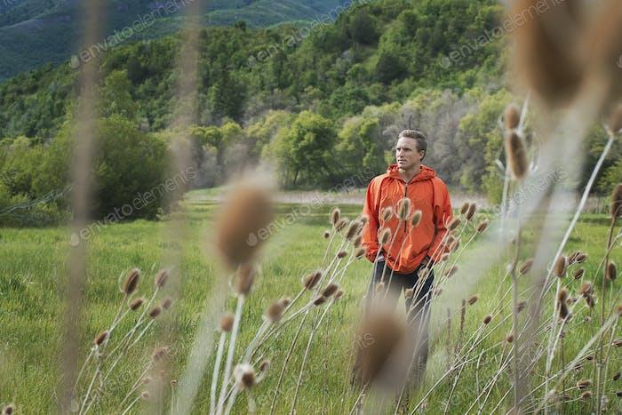 A man in an orange jacket walking his property.