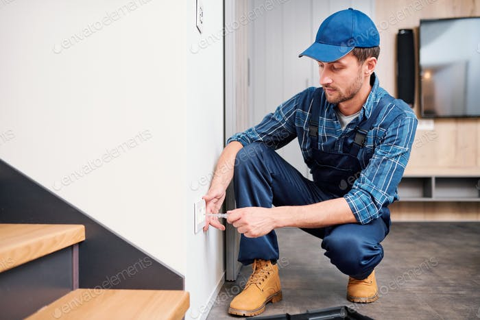 Young electrician from household maintenance service checking voltage of socket