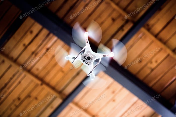White drone flying inside the building.