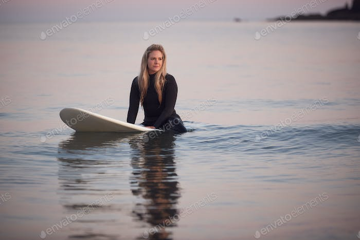 Woman Wearing Wetsuit Sitting And Floating On Surfboard On Calm  Sea