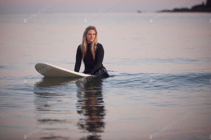Frau trägt Neoprenanzug sitzend und schweben auf surfbrett auf ruhig meer
