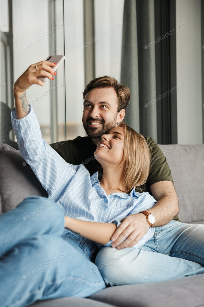 Photo of joyful couple smiling and taking selfie photo on cellphone
