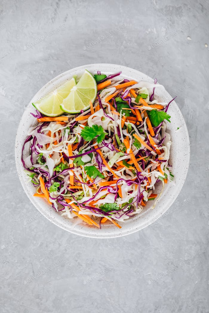 Cilantro lime coleslaw salad with red and white cabbage on stone background