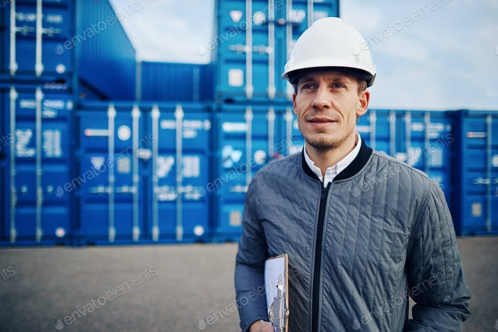 Smiling freight foreman standing on a large commercial shipping dock