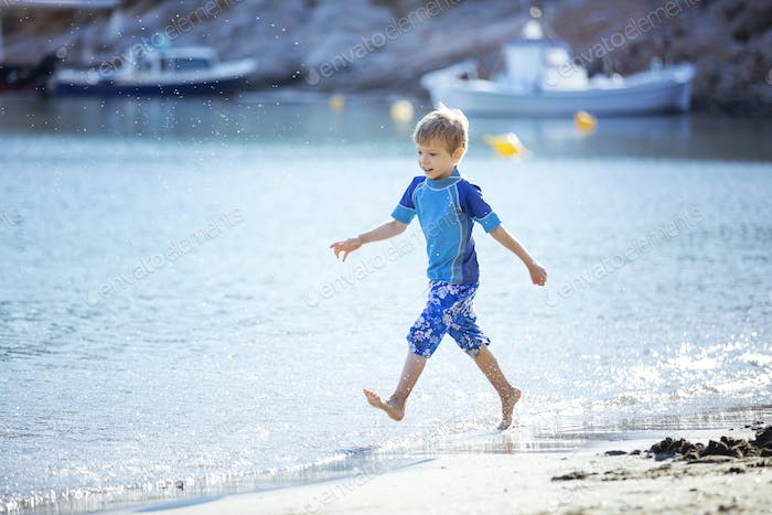 Happy young boy running along water edge  and making splashes