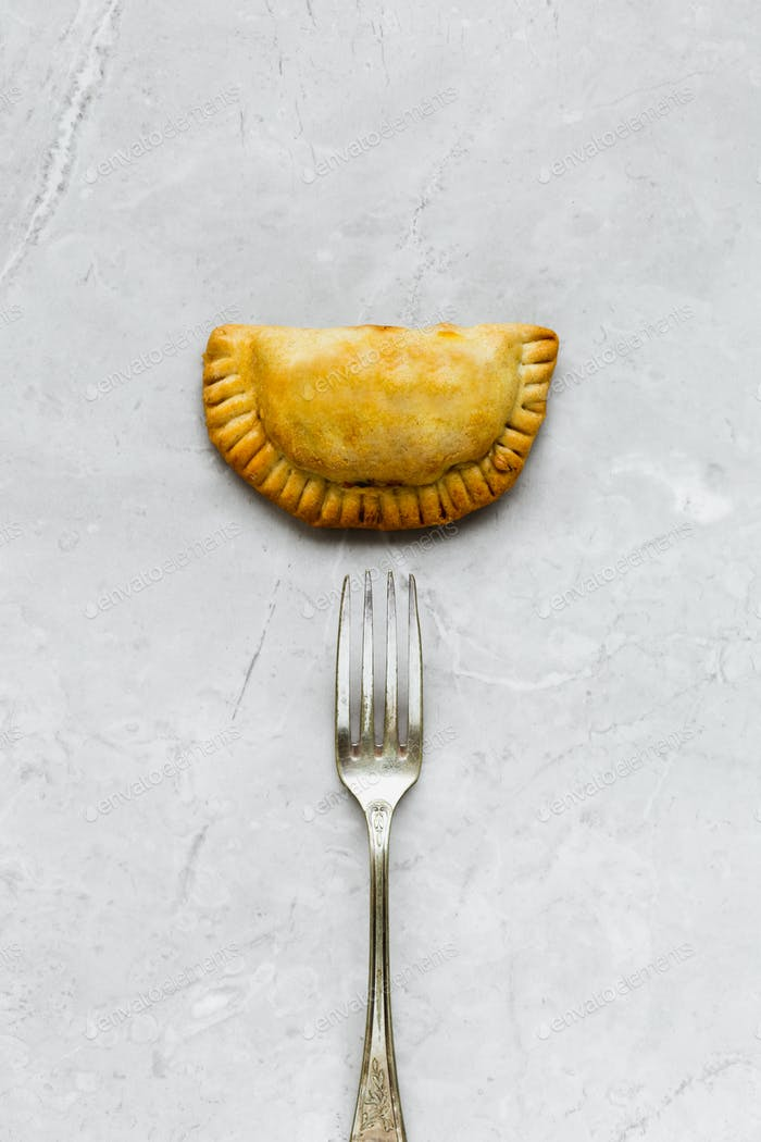 Top View of Empanada and Fork on Grey Marble Table