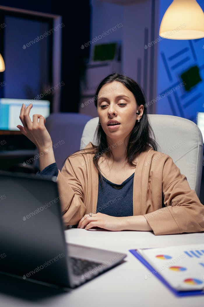 Businesswoman using earbuds in the course of online call