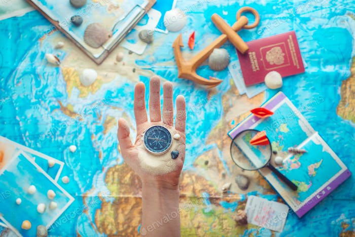 Hand holding a compass above map with wooden anchor, paper airplanes, passport and a magnifying