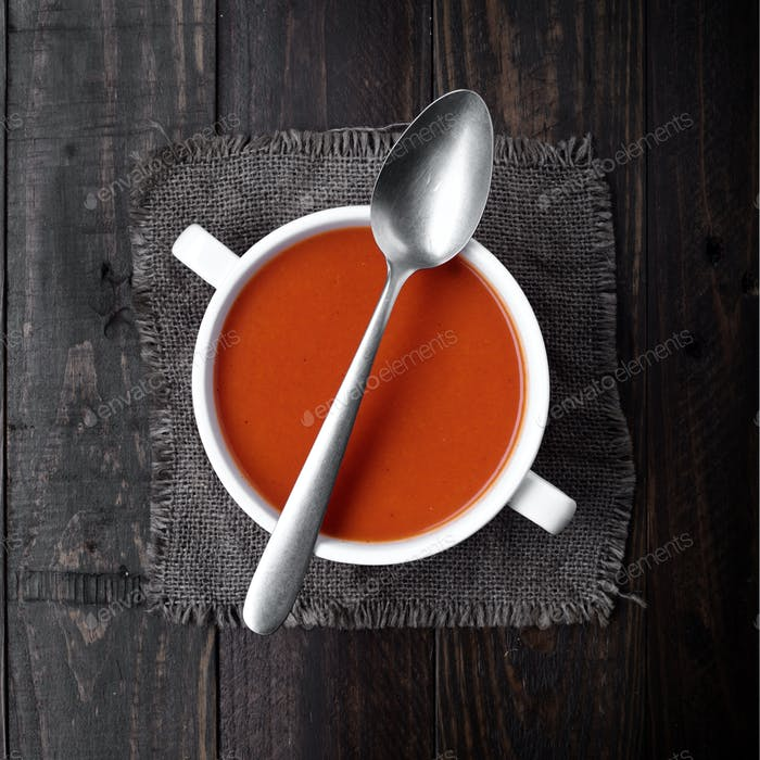 bowl of tomato sauce with spoon on rustic wood with natural light