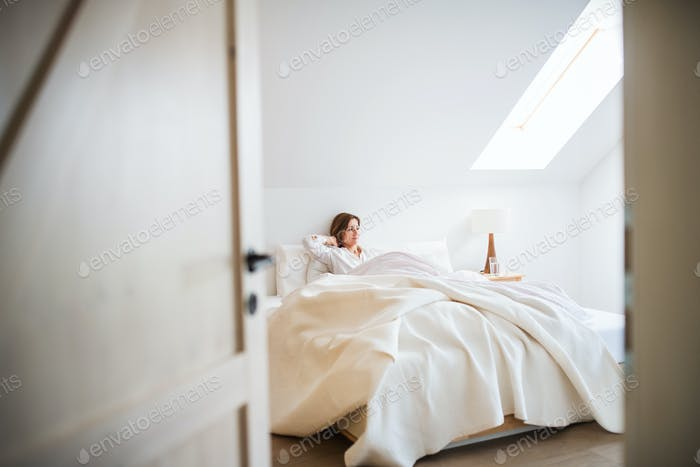 A young woman sitting in bed indoors in the morning in a bedroom, resting.