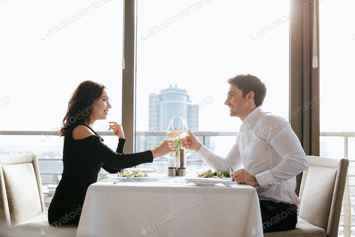 Cheerful loving couple sitting in restaurant indoors