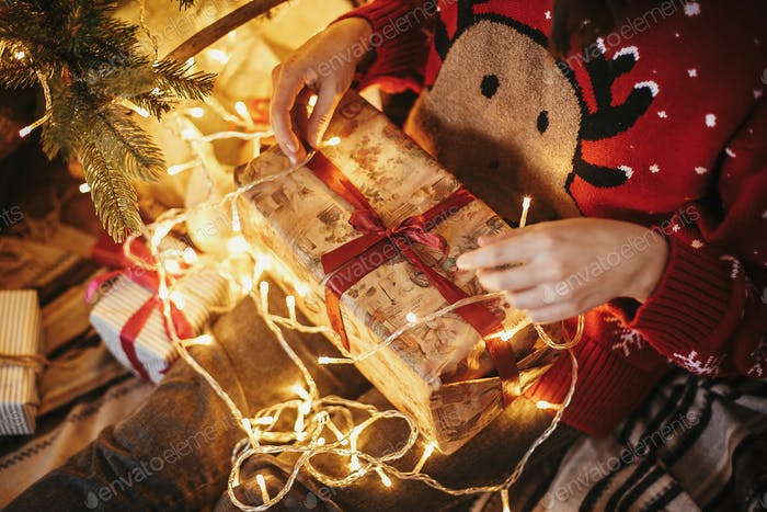 girl hands opening Christmas gift box on at golden beautiful christmas tree