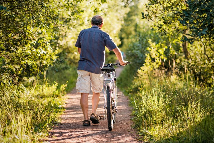 Mature man is walking in forest path with the bike