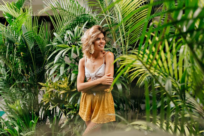 outside portrait of young adorable blond lady with short curly hairstyle  among tropical plants