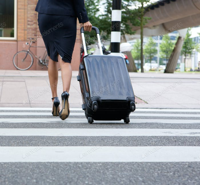 Businesswoman crossing street with luggage