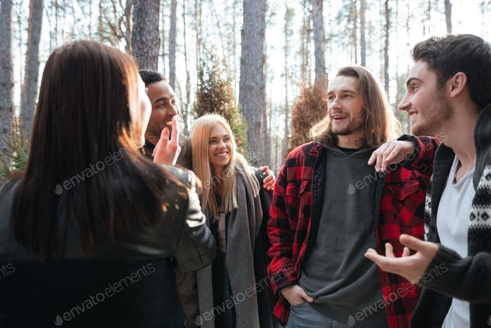 Cheerful group of friends standing outdoors in the forest