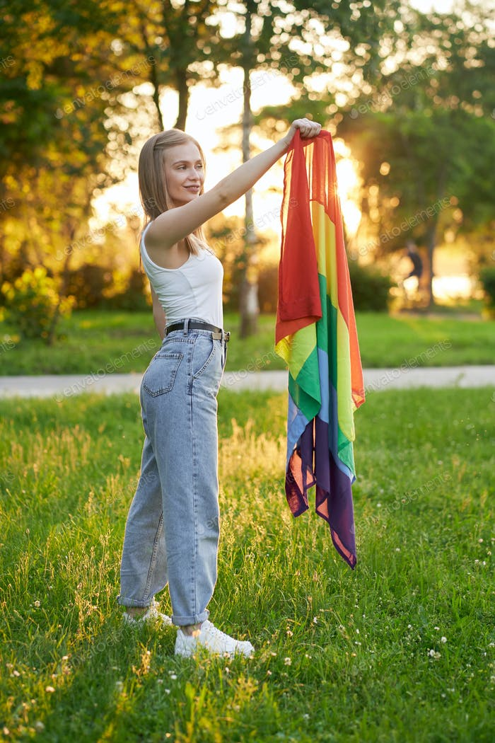 Smiling tolerant woman holding lgbt rainbow flag