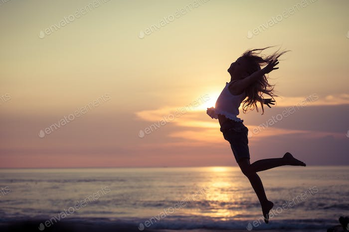 Happy little girl  jumping on the beach