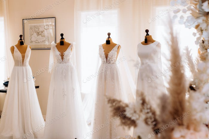 beautiful white wedding dresses hang on mannequins