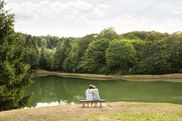 Senior couple on a walk at the lake hugging.