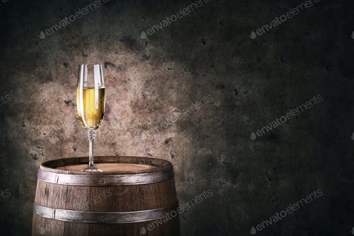 Glass of white wine on wooden barrel