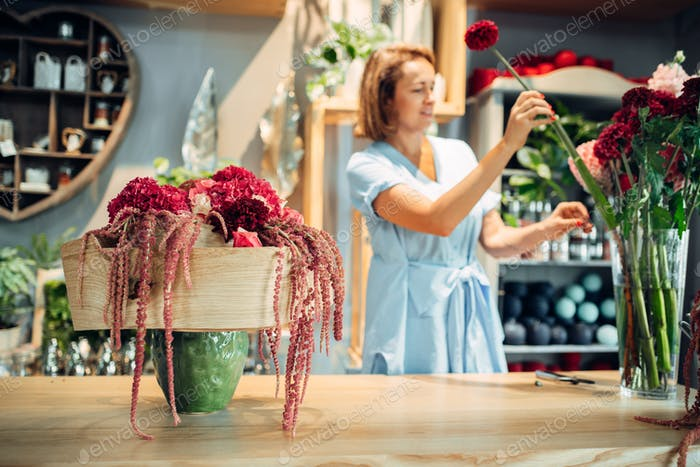 Female florist decorates flowers in shop