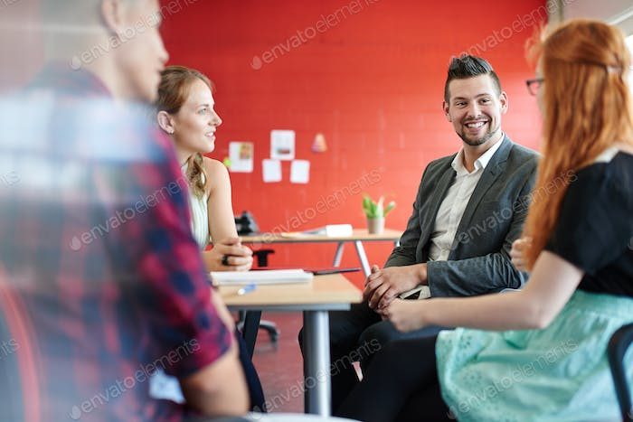Unposed group of creative business people in an open concept office brainstorming.