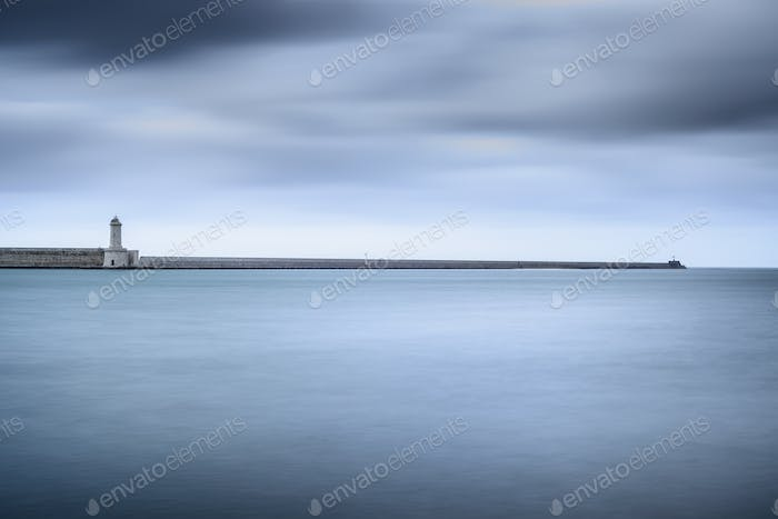 Livorno port lighthouse, breakwater and soft water under cloudy