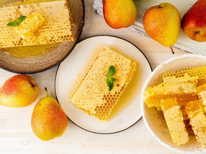 honey in honeycomb, close-up, on brown ceramic plate, on white wooden rustic table, top view.