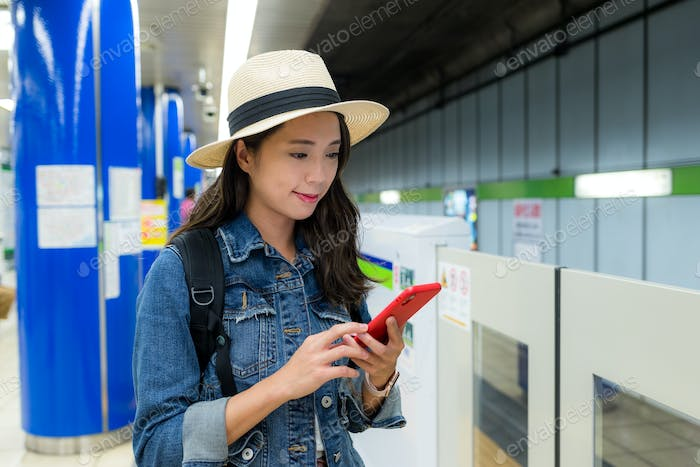 Woman use of mobile phone on train platform