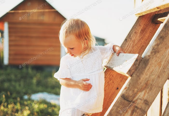 Cute blonde toddler little girl climbs up ladder, country side, cottagecor